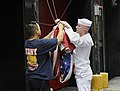 US Navy 090912-N-0413R-370 Intelligence Technician 2nd Class James Alcorn and New York City fireman Henry Gullotti raise colors over the fire station of Engine 8, Ladder 2, 8th Battalion in New York.jpg