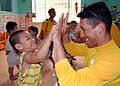 US Navy 100812-N-8539M-139 Operations Specialist 3rd Class Angel Ramirez practices high-fives with a child at a Da Nang primary school.jpg
