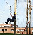 US Navy 100922-N-8848T-846 Officer Candidate Molly Carrigan, from Reno, Nev., zips down a line on the final station of the new 39-foot-tall high ro.jpg