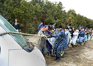 US Navy 110319-N-2653B-047 Service members and Misawa residents pull a damaged vehicle from the woods near the Misawa port.jpg
