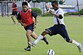 US Navy 110816-N-GV123-069 Culinary Specialist 2nd Class Michelot Joseph dribbles the ball past a Republic of Korea navy sailor during an exhibitio.jpg