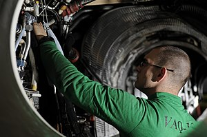 US Navy 120108-N-RG587-101 Aviation Structural Mechanic Airman Ryan Hollifield, assigned to Electronic Attack Squadron (VAQ) 134, cleans the engine.jpg