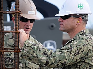 US Navy 120131-N-IA881-007 Construction Electrician 2nd Class Joshua Guerreiro shows Chief Builder Eric Van Norman, assigned to 25th Naval Construc.jpg