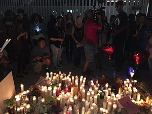 It is night time, a crowd of people are gathered around a candle vigil.