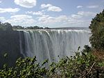A view of dozens of waterfalls side-by-side crashing into the water below. A rainbow forms at the right.