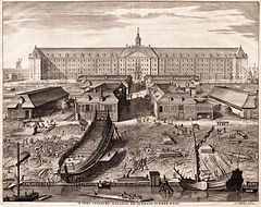 The shipyard of the Dutch East India Company (VOC) in Amsterdam (1726 engraving by Joseph Mulder).  The shipbuilding district of Zaan, near Amsterdam, became one of the world's earliest known industrialized areas, with around 900 wind-powered sawmills at the end of the 17th century. By the early 17th century Dutch shipyards were producing a large number of ships to a standard design, allowing extensive division of labour, a specialization which further reduced unit costs.