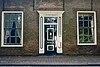 foto van Voormalig rechthuis. Huis van begane grond onder een hoog schilddak met het nr. 38. IJsselstenen gevel met rode strekken boven de vensters. Ingang in omlijsting van verdiepte pilasters met hoofdgestel. Mooi gesneden Lod. XVI deur. Vensters met twaalfruitsschuiframen, staafankers