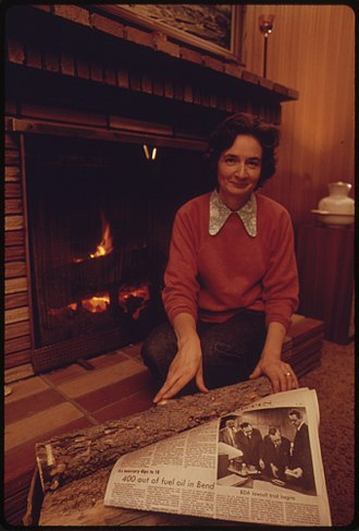 1973 oil crisis - A woman uses wood in a fireplace for heat. A newspaper headline before her tells of the community's lack of heating oil.
