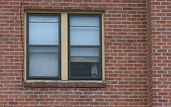 English: Windows in the red brick wall of an a...