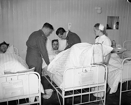 British wounded being treated at a hospital in Namsos by British and French medical officers and a Norwegian nurse Woundedatnamsos.jpg