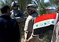 060311-N-6901L-136 - Iraqi flag adorns Iraqi soldier's uniform as U.S. Army soldier and an interpreter talk with a local farmer, during a mission to deliver anti-terrorist leaflets and information to residents.jpg