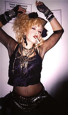 c536800fef Una mujer vestida como Madonna con el estilo que caracterizó a la cantante  en los años de 1980. Fue en esa década que se originó el término «Madonna  ...