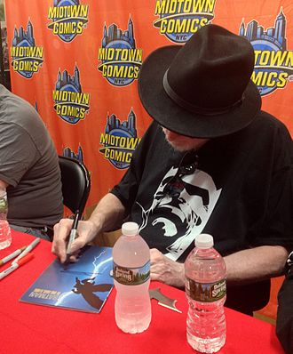 The Dark Knight Returns - Miller signing a copy of the book during a 2016 appearance at Midtown Comics