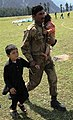 A Member of the Pakistan Military Carries a Baby While Escorting a Young Boy (4866213822).jpg