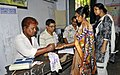 A polling official administering indelible ink to a voter, at a polling booth, during the fourth phase of West Bengal Assembly Election, at Shibpur, district Howrah on April 25, 2016.jpg