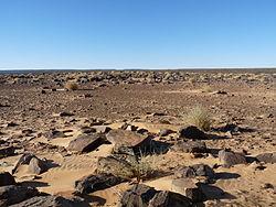 Photographie/ De gros cailloux aux bords tranchants parsèment une surface horizontale, quelques très petites accumulation de sable