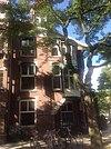 foto van Hoekpand (dubbelpand) met twee verdiepingen onder een samenstel van dwarsgeplaatste zadeldaken met licht overstek