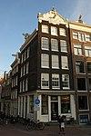 foto van Hoekhuis met gevel onder gebeeldhouwde zandstenen verhoogde lijst