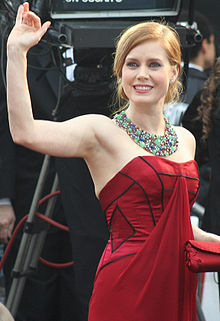 Young, blond woman wearing a red strapless dress and ornate gemstone necklace, smiling and waving.