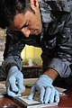 An Iraqi police officer uses tape to pull fingerprints from an object during a training exercise at Camp Ramadi, Iraq, March 1, 2011 110301-A-TO648-009.jpg