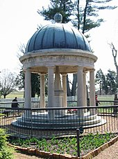 A tomb in a garden covered by a circular roof