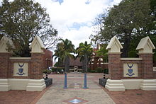 A brick wall with a gap in the middle. Through the gap one can see a statue at the bottom of a palm-lined walkway.