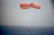 Spaceship descends over ocean with parachutes