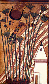 Painting of a cow whose head protrudes from a hill, in front of which stand papyrus stalks and a pyramidal chapel