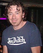 "A man with short brown hair wearing a blue t-shirt with ""Von Dutch"" written on it"