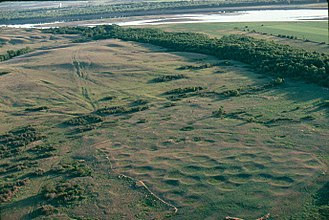 Like-a-Fishhook Village - Big-Hidatsa. Aerial view of the old Hidatsa village named Big Hidatsa at Knife River. Each depression shows the site of an earth lodge. Lack of timber and attacks by the Sioux forced the Hidatsa to build a new village at Like a Fishhook Bend.