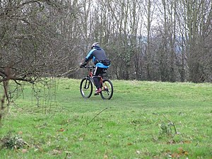 English: Biking along the path Person making t...