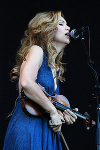 A woman in a blue dress holding a fiddle sings into a microphone