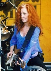 A woman with curly red hair wearing a blue shirt holding a guitar.