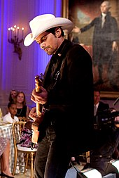 A man wearing a dark jacket and white cowboy hat playing guitar in front of an audience