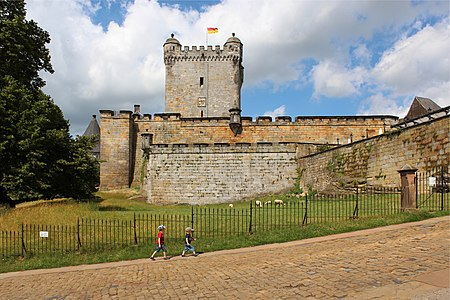 """Young tourists in front of the 11th/12th century """"Pulverturm"""", Burg Bentheim, Germany."""