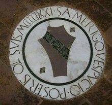 Photographie d'une pierre tombale au centre de laquelle se trouve un écu familial et autour de laquelle il est écrit «S. Amerigo Vespucio Posteris o suis MCCCCIXXI.»
