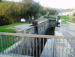 A narrow canal lock with the bottom gate open.