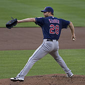 "A man, wearing a dark blue baseball cap, a dark blue baseball jersey with the number 28 and the words ""KLUBER"" across the back and grey pants, delivers a pitch from the mound."