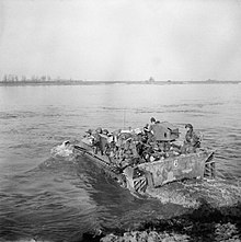 A black and white image of soldiers crossing a body of water in an amphibious vehicle