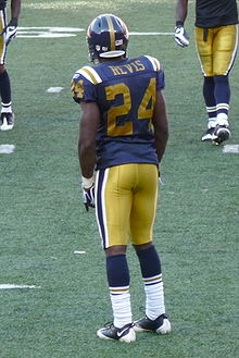 63cf7c954 Cornerback Darrelle Revis wearing the New York Titans throwback uniform.  This design combined the original shade of gold from 1960 with the 1961–62  striping ...