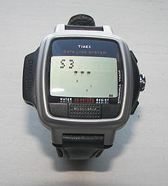Datalink USB Dress edition with Invasion video game, (one of eighteen posible modes). (Three lives remaining). The display is dot matrix. The watch crown (icontrol) can be used to move the defender left to right and the fire control is the Start/Split button on the lower side of face of the watch at 6 o' clock. The pixels of the invaders appear slightly blurred upon picture magnification because of the animation of the aliens. The faint pixels diagonally to the left of the defender block are pixel traces of alien missiles. This Datalink model is waterproof to 30 m.