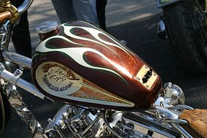 """Indian Larry - Wild Child chopper which Larry said in 2003 was the best bike he'd """"ever built"""". Features root beer metal flake paint; also visible is the chromed, twisted down tube and two different head styles on the engine."""