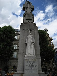 A marble statue of Edith Cavell in nurse's uniform backed by a large granite column, surmounted by a figure representing Humanity