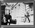 Elihu Root, walking toward automobile and chauffeur LCCN97513837.jpg
