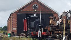 Brick building with steam locomotives in front of it.