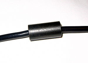 "Inductor - A ferrite ""bead"" choke, consisting of an encircling ferrite cylinder, suppresses electronic noise in a computer power cord."