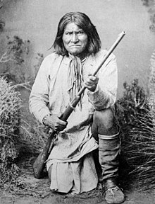 Geronimo (Goyathlay), a Chiricahua Apache, full-length, kneeling with rifle, 1887 - NARA - 530880.jpg