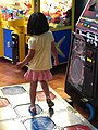 Girl playing Legacy Dance dance revolution cabinet.jpg