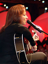 The side view of a woman with her eyes closed, singing into a microphone and playing a black guitar.