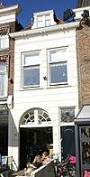 foto van Gepleisterd lijstgeveltje met poort. Huis onder schilddak, waarin dakvenster met vleugelstukken